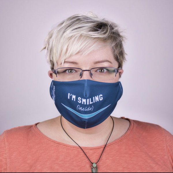 """picture of Mel wearing a dark teal face covering over her mouth and nose that says """"I'm Smiling (inside)"""" with a light teal smile"""