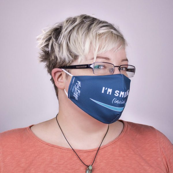 """picture of Mel looking to the side wearing a dark teal face covering over her mouth and nose that says """"I'm Smiling (inside)"""" with a light teal smile, and """"Mel Biggs Music"""" logo"""